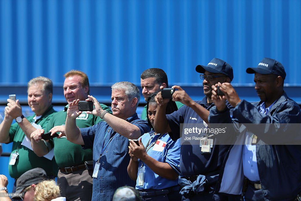 Workers take pictures as President Barack Obama speaks during an event at PortMiami on March 29, 2013 in Miami, Florida. The president spoke about road and bridge construction during the event at the port in Miami, where he also toured a new tunnel project.