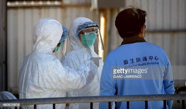 Workers talk during a chicken cull in Hong Kong on December 31 after the deadly H7N9 virus was discovered in poultry imported from China Hong Kong...