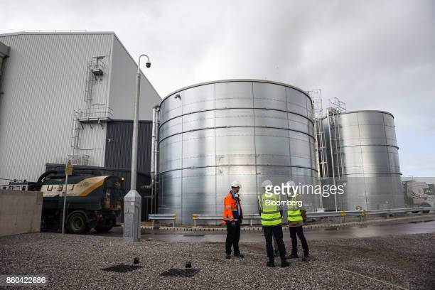 Workers talk in front of sprinkler tanks at the Renesciencewaste energy plantoperated by Dong Energy A/S in Northwich UK on Thursday Oct 5 2017 The...