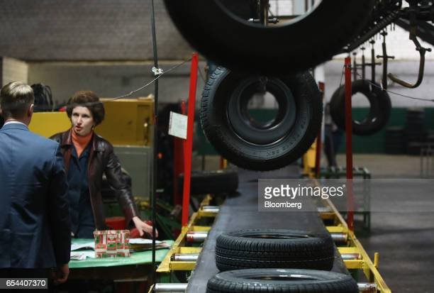 Workers talk in the control room as newly manufactured rubber tires for the automobile industry pass along a conveyor belt at the Belshina JSC tire...