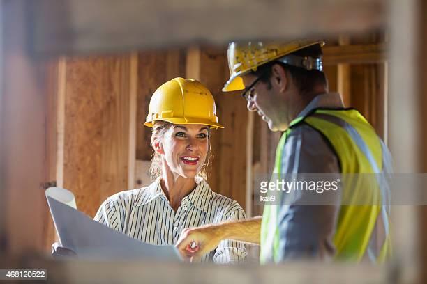 Arbeiter, die auf der Baustelle Pläne überprüfen.