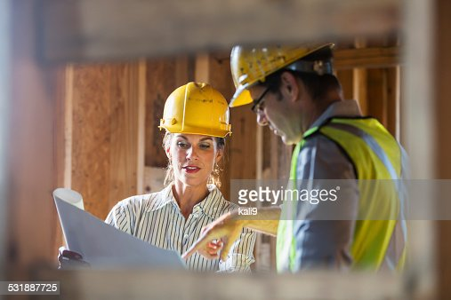 Workers talking at construction site reviewing plans