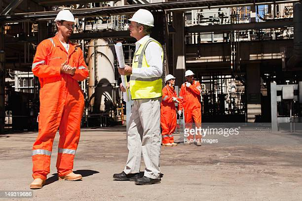 Workers talking at oil refinery