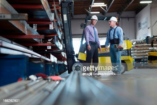 Workers talking in metal plant : Stock Photo