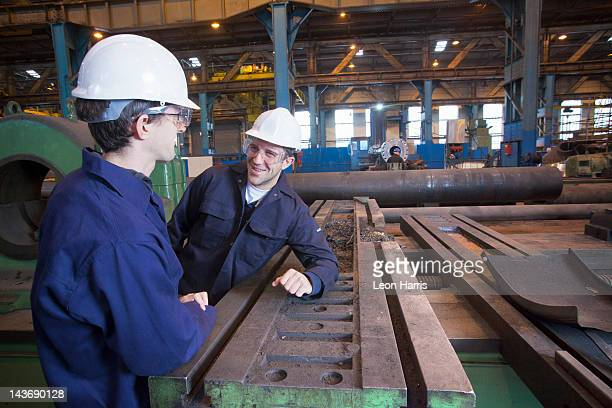 Workers talking in steel forge