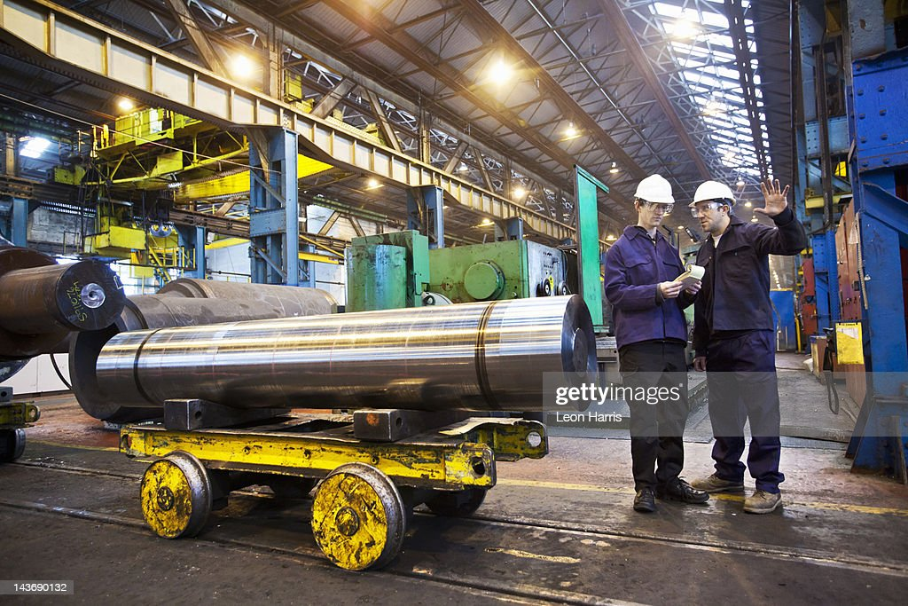 Workers talking in steel forge : Stock Photo