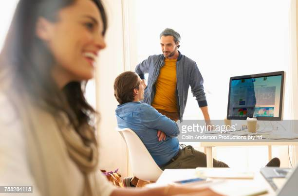 Workers talking near computer in office