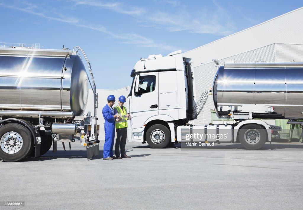 Workers talking next to stainless steel milk tankers