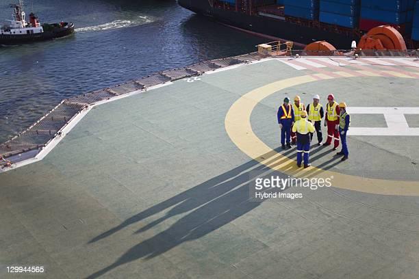 Workers talking on helipad of oil rig