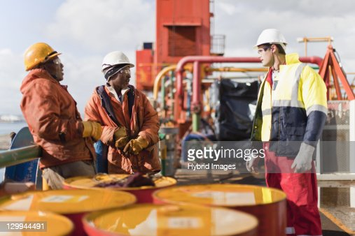 Workers talking on oil rig