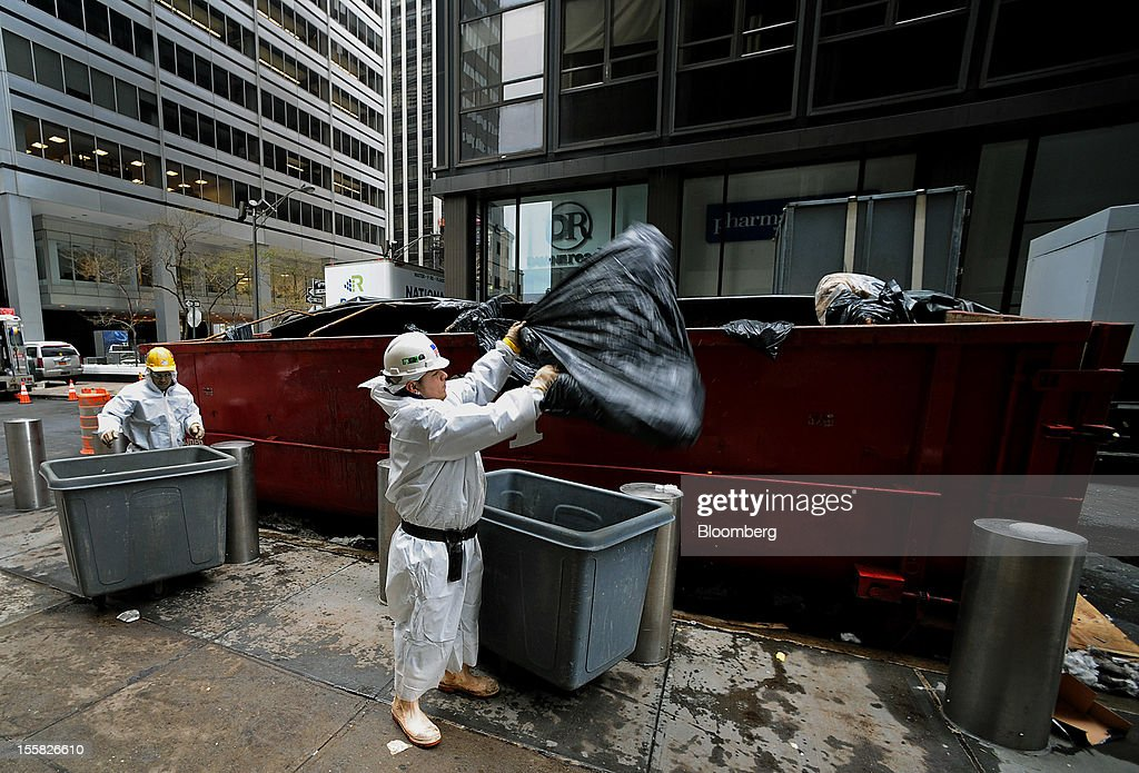 Workers throw out property damaged by water in the lower Manhattan area of New York, U.S., on Thursday, Nov. 8, 2012. New York-area residents shoveled several inches of snow and airlines prepared to resume flights as the region coped with a nor'easter that slowed the recovery from superstorm Sandy. Photographer: Peter Foley/Bloomberg via Getty Images