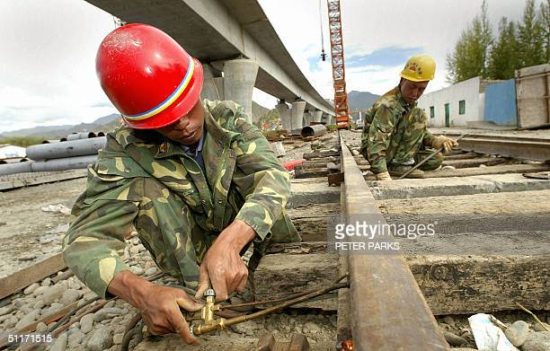 Workers toil under the railway bridge spanning the Lhasa River part of the 1532km long QinghaiTibet railway outside of Lhasa 14 August 2004 The...
