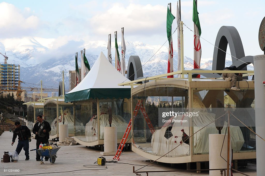 Workers touch up a display of the cars wrapped in symbolic burial shrouds that were destroyed during the assassinations that killed several Iranian...