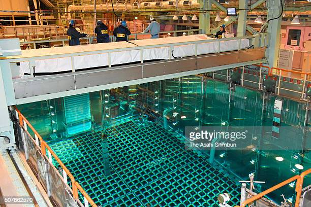 Workers transfer stored fuel rods into the No4 reactor at the Kansai Electric Power Co's Takahama Nuclear Power Plant on January 31 2016 in Takahama...