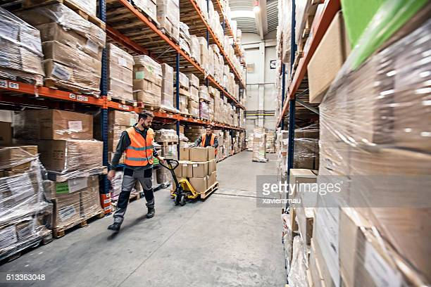 Workers transporting boxes in warehouse