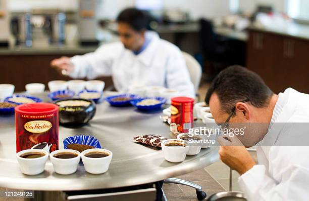 Workers try Tim Hortons Inc coffee samples in a quality control room at the company's roasting plant in this photo taken with a tiltshift in Ancaster...
