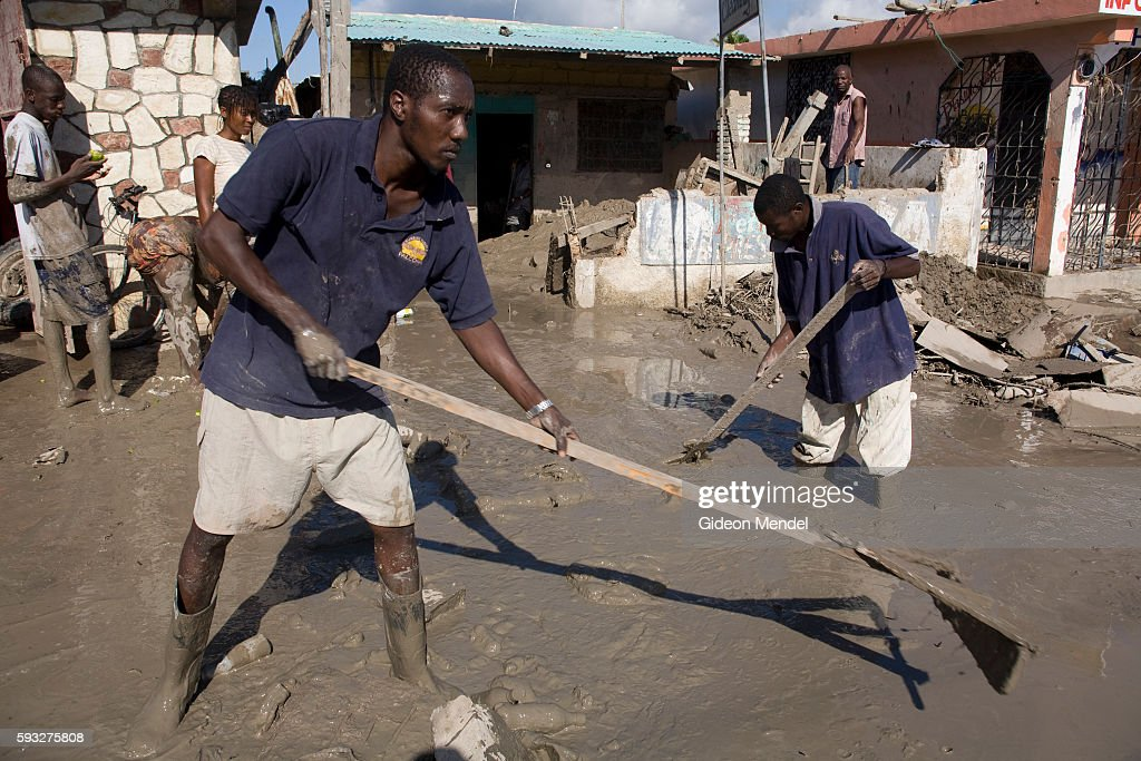 Workers try to clear the mud away from the front of a small dry cleaning business in Gonaives Two weeks earlier the entire city had been flooded...