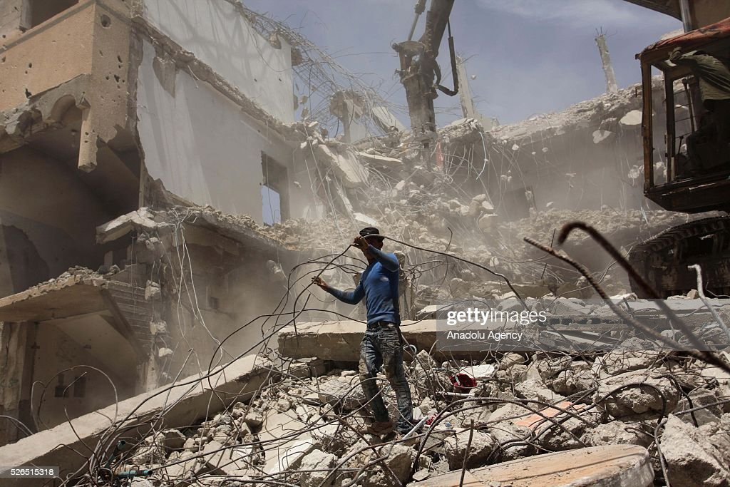 Workers try to gather old reinforcing bars from wreckage of buildings, destroyed by Israeli forces, as reconstruction works continue at Shuja'iyya Neighborhood of Gaza City, Gaza on April 30, 2016.