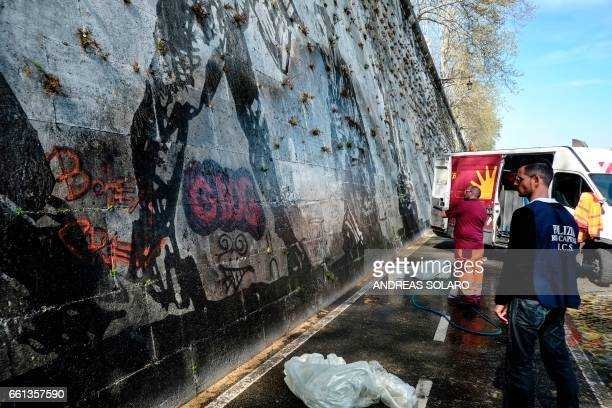 Workers try to remove graffiti on the 'Triumphs and Laments' fresco which was completed along the banks of Romes Tiber river less than a year ago by...