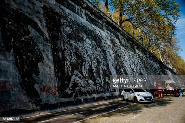 Workers try to remove graffiti on the 'Triumphs and Laments' frescoe which was completed along the banks of Romes Tiber river less than a year ago by...