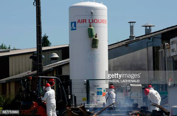 Workers try to take gas cylinders off an Air Liquide gas holder at the site of ailing car parts factory GmS Industry factory in La Souterraine...