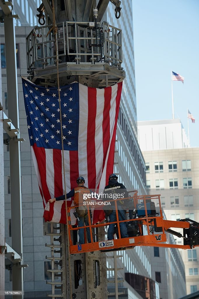 Workers unfurl a flag as the final sections of the spire is raised to the top of One World Trade Center May 2, 2013 in New York to a temporary work platform atop the structure. Ironworkers will install the sections at a later date and when complete, One WTC will stand 1,776 feet (541 meters) high, making it the tallest building in the Western Hemisphere. AFP PHOTO/Stan HONDA