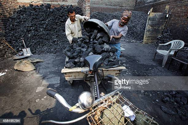Workers unload a metal basin of coal onto a bicycle trailer at a wholesaler in New Delhi India on Wednesday Nov 5 2014 Prime Minister Narendra Modi...