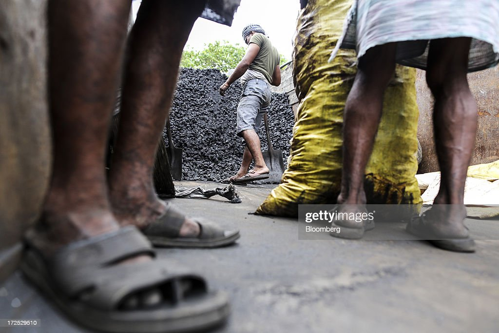 Workers unload a truck at a coal wholesale market in Mumbai, India, on Tuesday, July 2, 2013. India, the worlds third-largest coal consumer, imported 43 percent more of the fuel than a year ago on increased demand from power stations and steelmakers, according to shipping data, and is set to eclipse China as the top importer of power station coal by 2014. Photographer: Dhiraj Singh/Bloomberg via Getty Images
