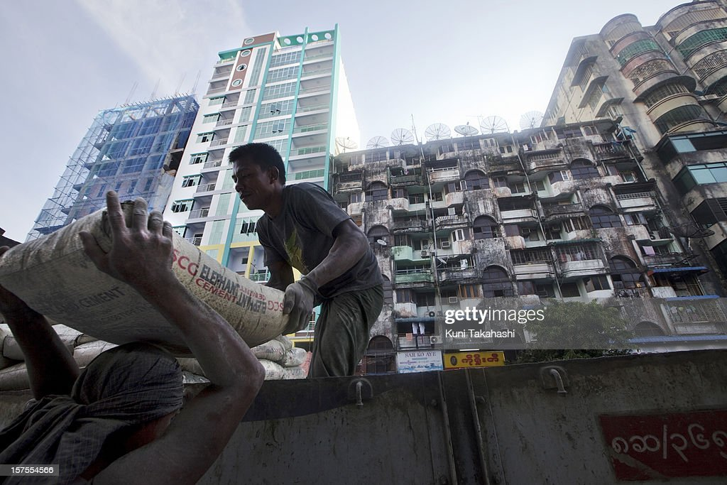 Workers unload bags of cement from truck in front of newly constructed buildings next to old housing in downtown on November 14, 2012 in Yangon, Myanmar. Myanmar's economy is predicted to grow by over 6.0% next year on the back of commodity exports and a increase in foreign investment.