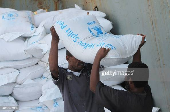 Workers unload bags of food from a UN's World Food Programme ship docked in Yemen's devastated port city of Aden on July 21 2015 as it brings in...