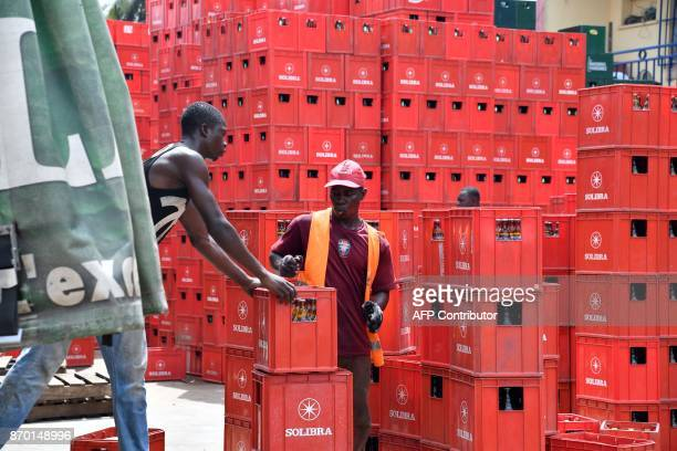 Workers unload beer bottles from a truck in the Abobo suburb of Abidjan Ivory Coast on November 4 2017 / AFP PHOTO / ISSOUF SANOGO
