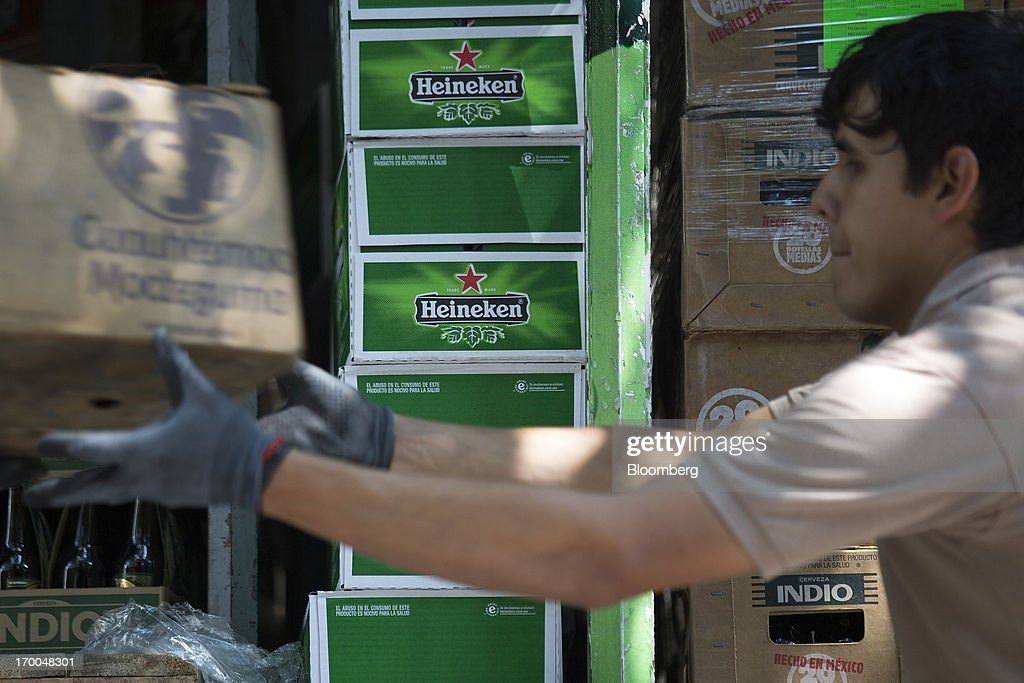 Workers unload beer from a truck operated by Cuauhtemoc-Moctezuma, a subsidiary of Heineken NV, while making deliveries in Mexico City, Mexico, on Thursday, June 6, 2013. Heineken NV and Grupo Modelo SAB, the dominant brewers in Mexico with brands such as Dos Equis and Corona, are nearing the end of an almost three-year-old government antitrust probe. Photographer: Susana Gonzalez/Bloomberg via Getty Images