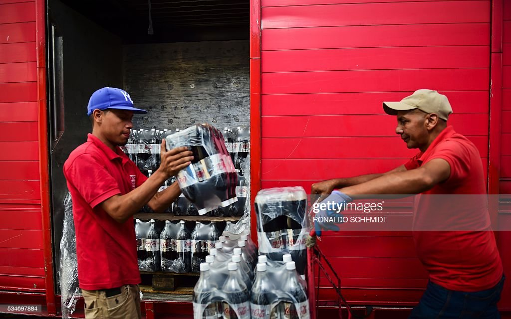Workers unload bottles of Coca Cola from a truck in Caracas on May 27, 2016. Coca Cola suspended much of its distribution in Venezuela due to a shortage of sugar. / AFP / RONALDO