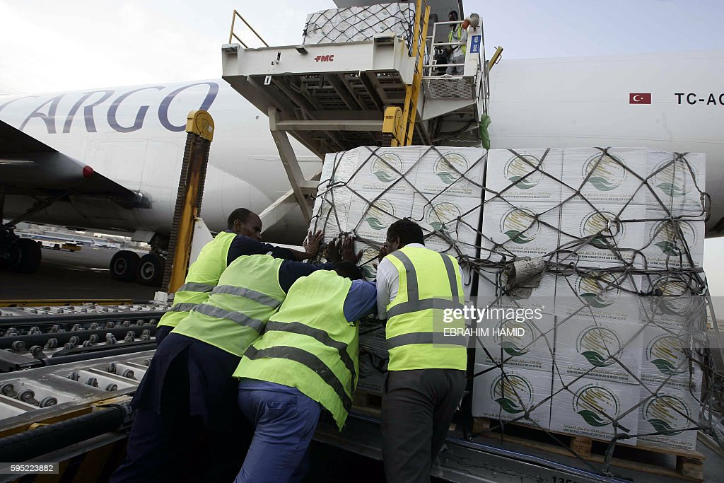 Workers unload boxes of aid from Saudi Arabia designated for the victims of the flood in Sudan on August 25 2016 at the Khartoum airport Thousands of...