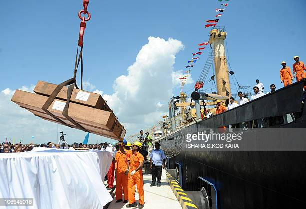 Workers unload cargo from the first vessel to enter the newlybuilt Chinesefunded port in Hambantota on November 18 2010 Sri Lanka's president Mahinda...