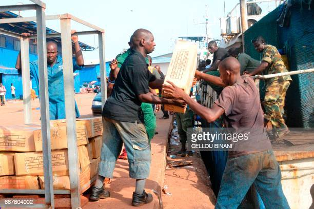 Workers unload cartons from two Chinese ships on April 11 2017 at the harbour in Conakry after an Guinea's authorities inspection Guinean inspectors...