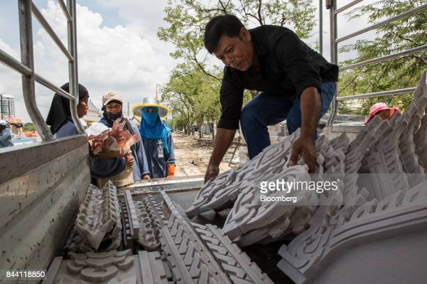 Workers unload carved masonry while preparing the ceremonial ground for King Bhumibol Adulyadej's cremation at Sanam Luang park in Bangkok Thailand...