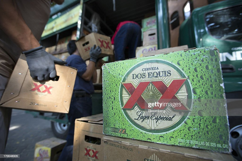 Workers unload cases of Grupo Modelo SAB's Dos Equis brand beer from a truck operated by Cuauhtemoc-Moctezuma, a subsidiary of Heineken NV, while making deliveries in Mexico City, Mexico, on Thursday, June 6, 2013. Heineken NV and Grupo Modelo SAB, the dominant brewers in Mexico with brands such as Dos Equis and Corona, are nearing the end of an almost three-year-old government antitrust probe. Photographer: Susana Gonzalez/Bloomberg via Getty Images