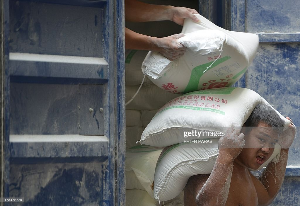 Workers unload flour on a street in Shanghai on July 15, 2013. China's gross domestic product expanded 7.5 percent in the April-June quarter, official data showed, a second consecutive slowdown in growth as worries mount over the health of the world's number two economy. AFP PHOTO/Peter PARKS