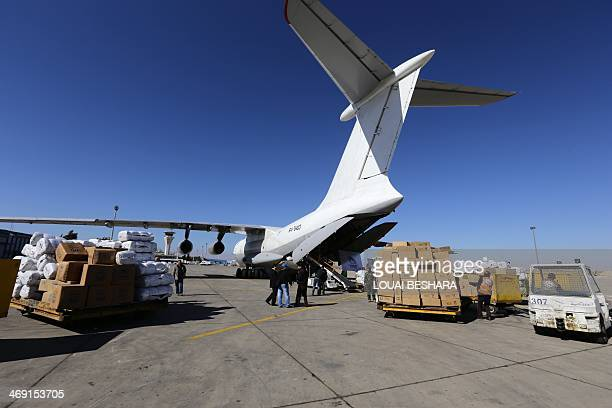 Workers unload from a cargo aircraft parcels of emergency relief provided by the United Nation's Refugee Agency on February 13 2014 at Damascus'...