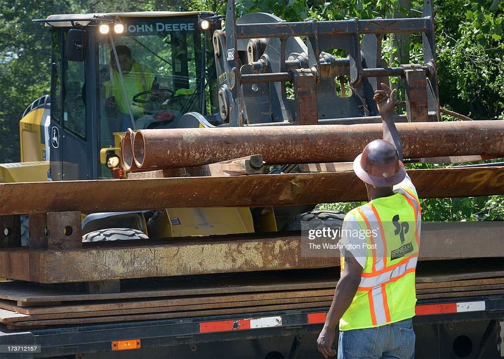 Workers unload pipes at the site of the defective water main as Prince Georges residents prepare for a break in water service during the hottest week of the year on July, 16, 2013 in Forestville, MD.