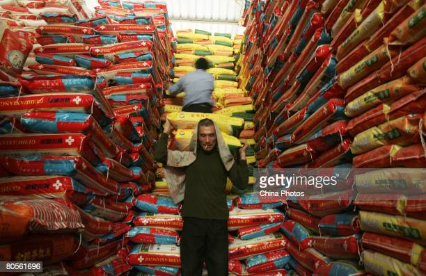 Workers unload rice at a farm product market on April 8 2008 in Wuhan of Hubei Province China According to the National Development and Reform...