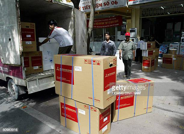 Workers unload room air conditioners from a truck in front of an electrical appliance shop in downtown Hanoi 22 June 2004 A wave of heat has been...