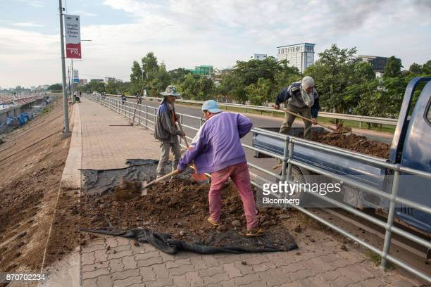 Workers unload soil from a truck at a roadside construction site in Vientiane Laos on Thursday Nov 2 2017 Located in the Mekong region Southeast...