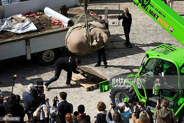 Workers unload the head of a sculpture of Russian revolutionary Vladimir Lenin for an exhibition of monuments in the citadel in Spandau district on...