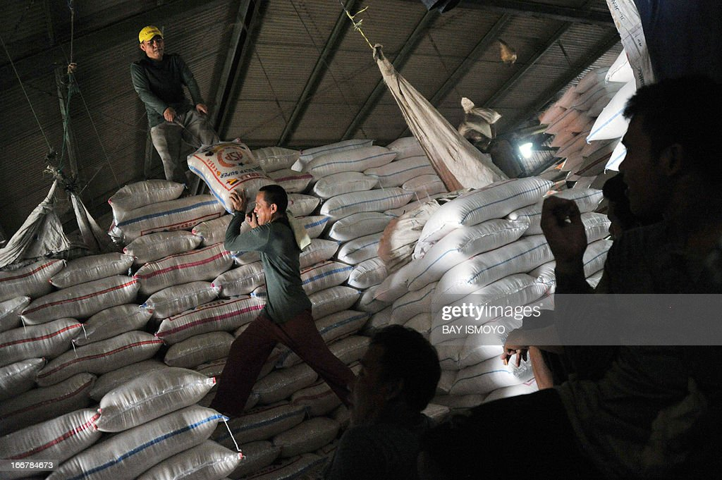 Workers unload tons of rice in sacks at a wholesale rice market in Jakarta on April 17, 2013. Indonesian inflation accelerated to 5.90 percent year-on-year in March, surpassing the upper limit of the central bank's target range due to an increase in food prices, official data showed early this month. AFP PHOTO / Bay ISMOYO