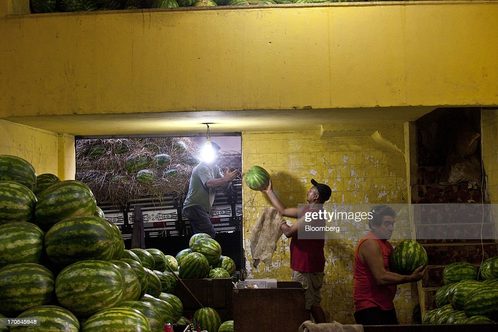 Workers unload watermelons at a market in Rio de Janeiro, Brazil, on Thursday, June 13, 2013. Brazilian retail sales rose in April at less than half the pace economists forecast as inflation erodes purchasing power, complicating the governments effort to boost growth. Photographer: Dado Galdieri/Bloomberg via Getty Images