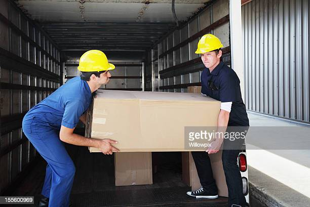 Workers Unloading Heavy Box