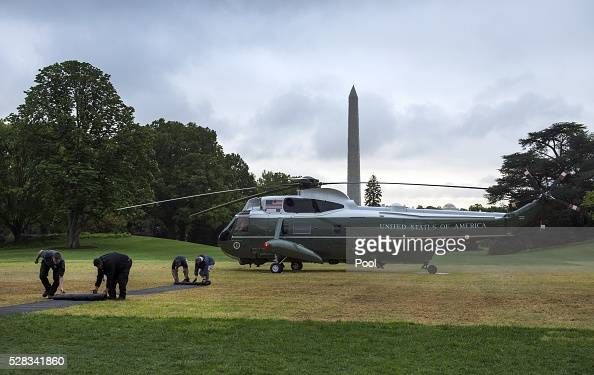 Workers unroll a mat for US President Barack Obama to walk on as he returns to the White House following a day trip to Flint Michigan on the South...