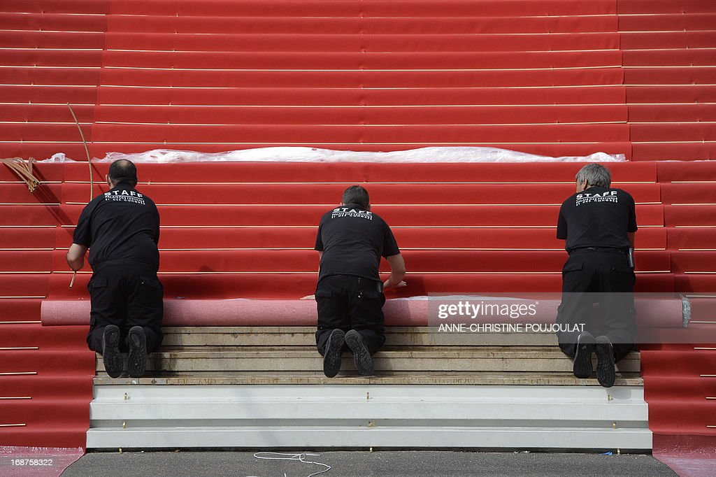 Workers unroll the red carpet at the entrance of the Palais des Festivals on the opening day of the 66th edition of the Cannes Film Festival on May 15, 2013 in Cannes. Cannes, one of the world's top film festivals, opens today and will climax on May 26 with awards selected by a jury headed this year by Hollywood legend Steven Spielberg.
